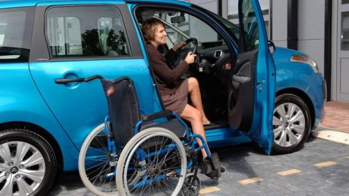 Wheelchair user next to her car