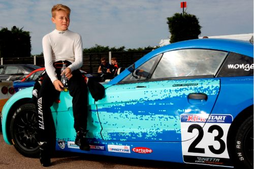 Billy Monger sitting on his racing car