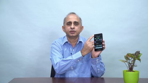 Pramit holding a phone and pointing to his app